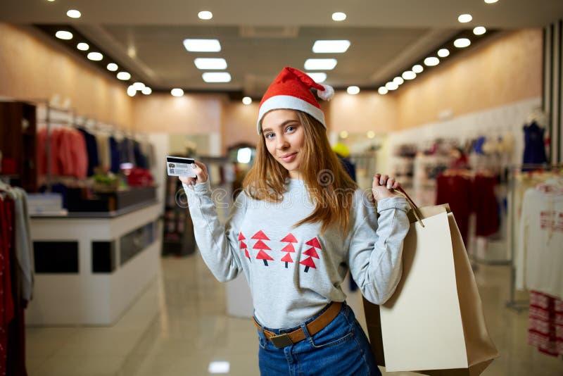 Jeune femme blonde heureuse dans le chapeau de Noël jugeant la carte de crédit et les sacs à provisions colorés, regardant la cam images stock