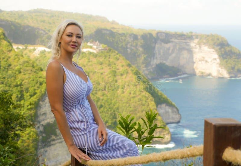 Jeune femme blonde heureuse et belle détendue au point de vue tropical de falaise de plage appréciant la fuite de vacances d'été  photo stock