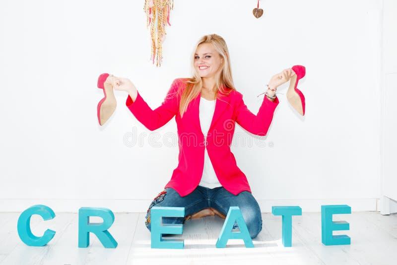 Jeune femme blonde heureuse jouant avec les talons hauts roses image libre de droits