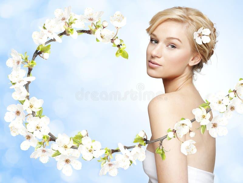 Jeune femme blonde magnifique avec la branche de fleur de ressort