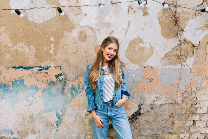 Jeune femme blonde magnifique posant avec la main dans la poche sur un fond grunge Jolie fille de sourire avec images stock
