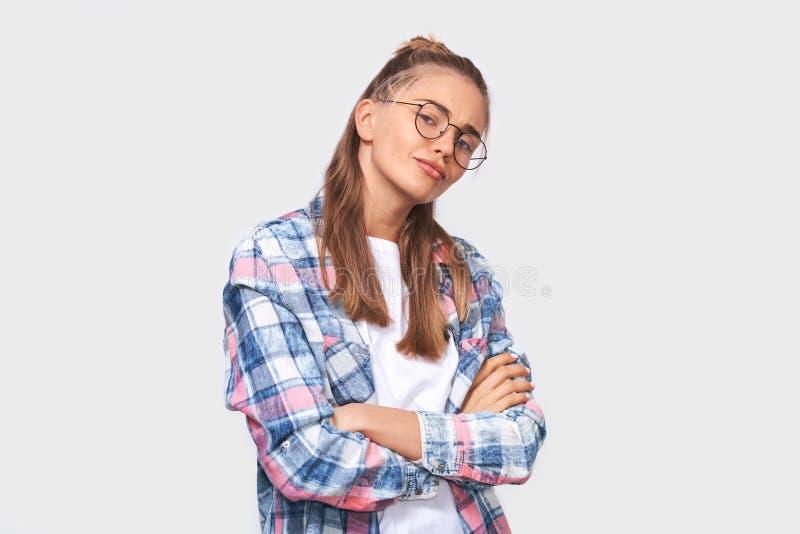 Jeune femme blonde magnifique regardant la caméra avec les mains croisées, l'équipement occasionnel de weraign et les lunettes ro photographie stock libre de droits