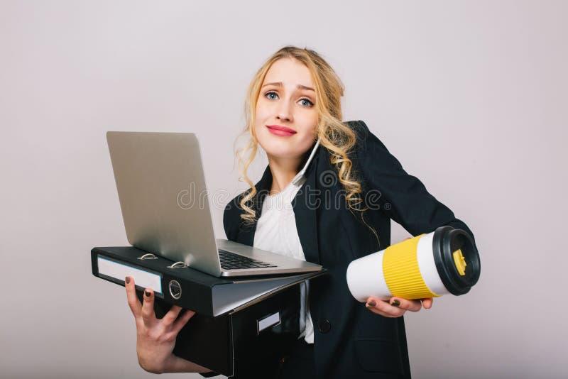 Jeune femme blonde mignonne de bureau dans la chemise blanche, veste noire, avec l'ordinateur portable, dossier, café à aller d'i photos libres de droits