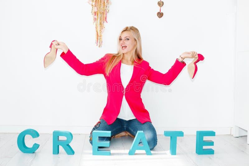 Jeune femme blonde moderne heureuse montrant les talons hauts roses image stock