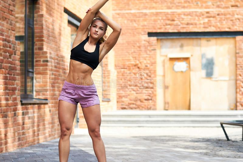 Jeune femme blonde musculaire forte dans des vêtements de sports faisant les courbures latérales photographie stock
