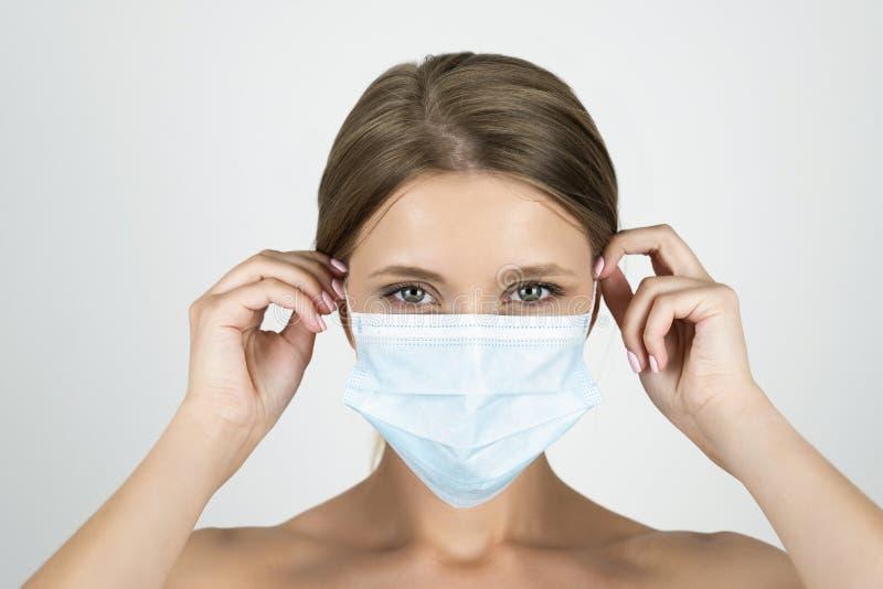 Jeune femme blonde portant le masque médical le fixant avec ses mains étroites vers le haut du fond blanc d'isolement photographie stock libre de droits