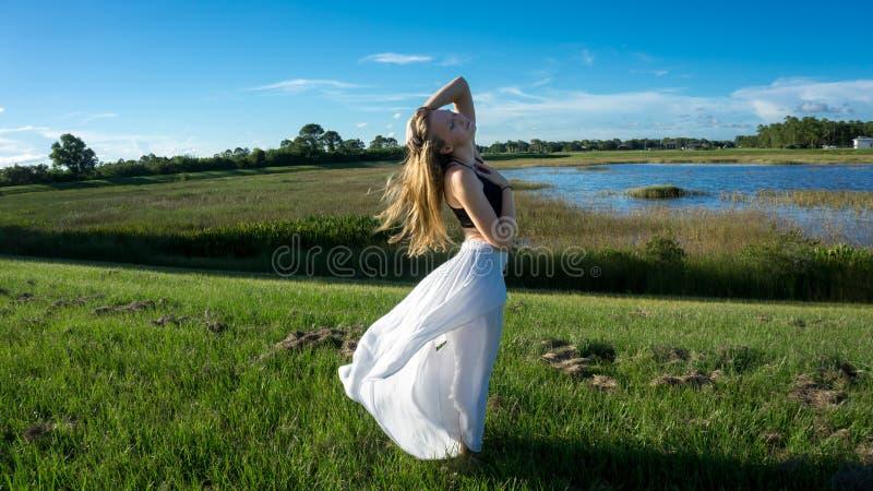 jeune femme blonde posant contre le vent dans le paysage avec le visage paisible pendant la jupe et les cheveux de coucher du sol photos stock