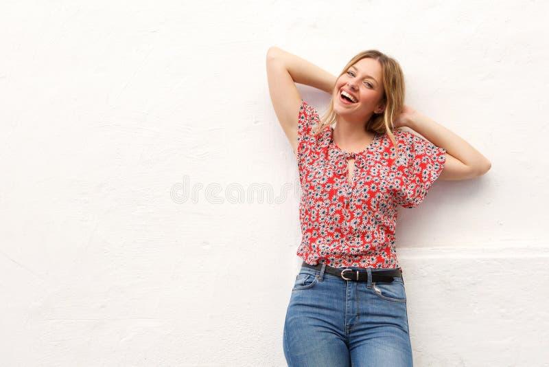 Jeune femme blonde riant avec des mains derrière la tête images stock