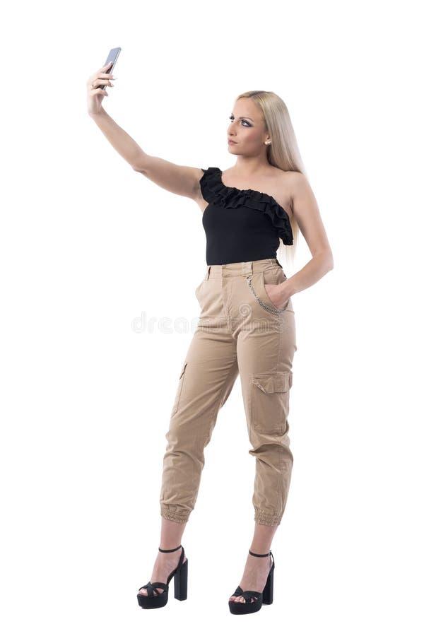 Jeune femme blonde sérieuse sûre dans le dessus noir sans manche prenant des selfies photo libre de droits