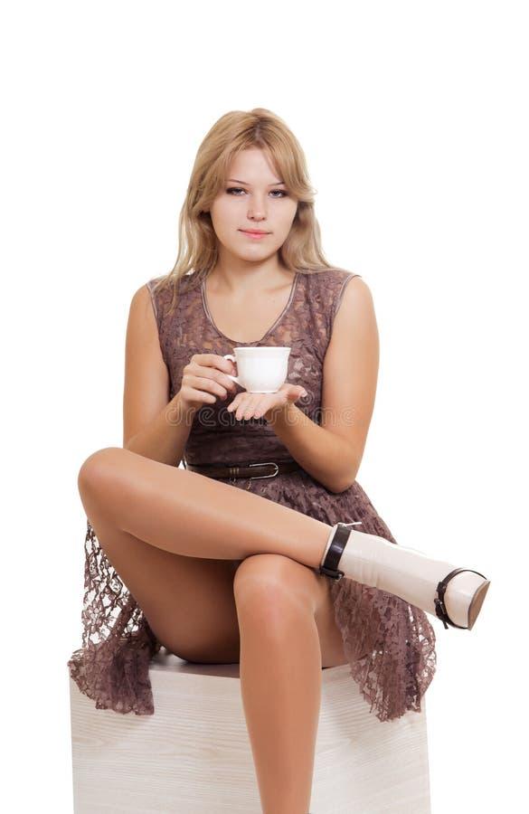 Jeune femme blonde s'asseyant avec la tasse de thé photographie stock