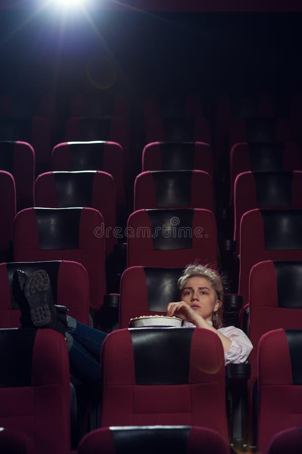 Jeune femme blonde s'asseyant dans la salle de cinéma photo stock