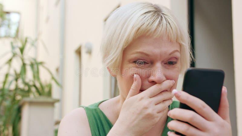 Jeune femme blonde s'asseyant en dehors et utilisant du téléphone photo stock
