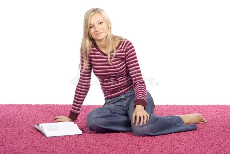 Jeune femme blonde s'asseyant sur le tapis rose avec le livre photographie stock