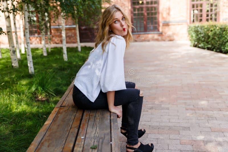 Jeune femme blonde se reposant sur le banc et les lèvres faites d'arc photo stock