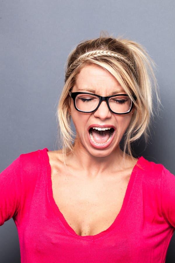 Jeune femme blonde sexy folle criant son exaspération photographie stock libre de droits