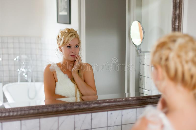 Jeune femme blonde sexy loking au miroir dans la salle de bains image libre de droits