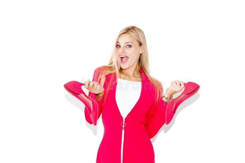 Jeune femme blonde shopaholic tenant les talons hauts roses photographie stock libre de droits