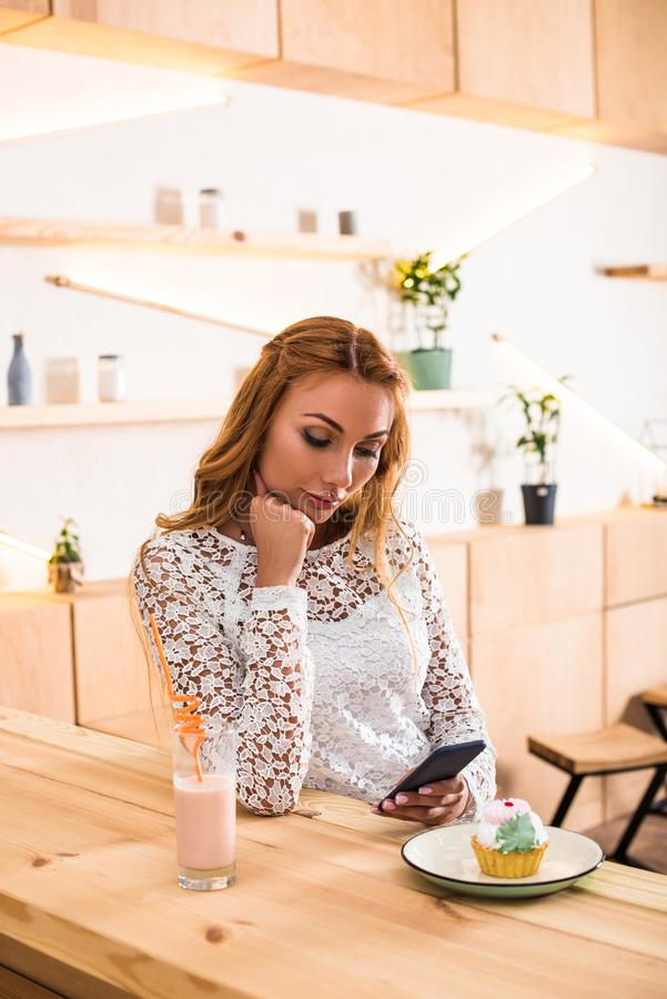 jeune femme blonde songeuse à l'aide du smartphone tout en se reposant photo stock