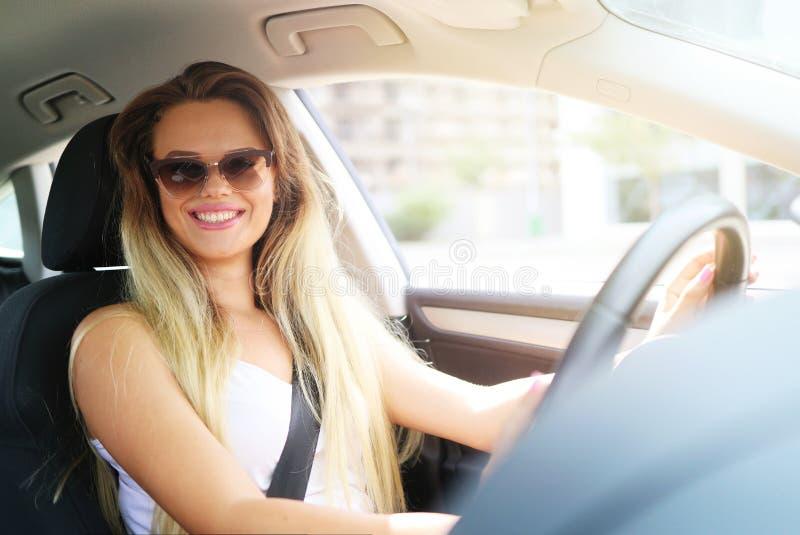 Jeune femme blonde souriant tout en conduisant une voiture Louez une voiture dans le concept de vacances photos libres de droits