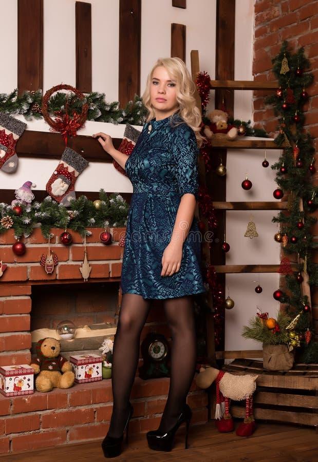 Jeune femme blonde tenant le concept proche d'hiver de chemin?e ? la maison image libre de droits