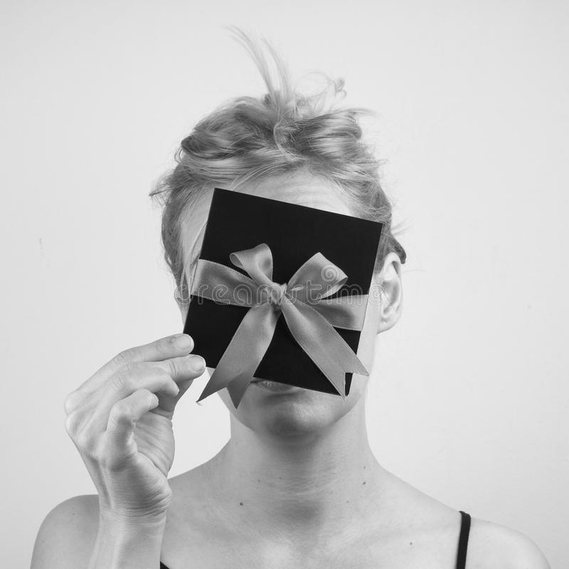 Jeune femme blonde tenant une carte avec le ruban devant son fa image stock