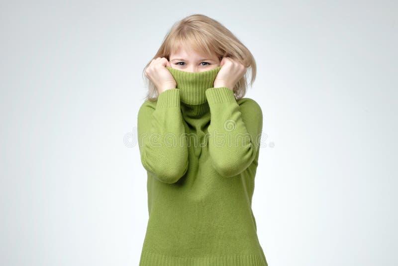 Jeune femme blonde utilisant un haut chandail de vert de cou cachant son visage image stock