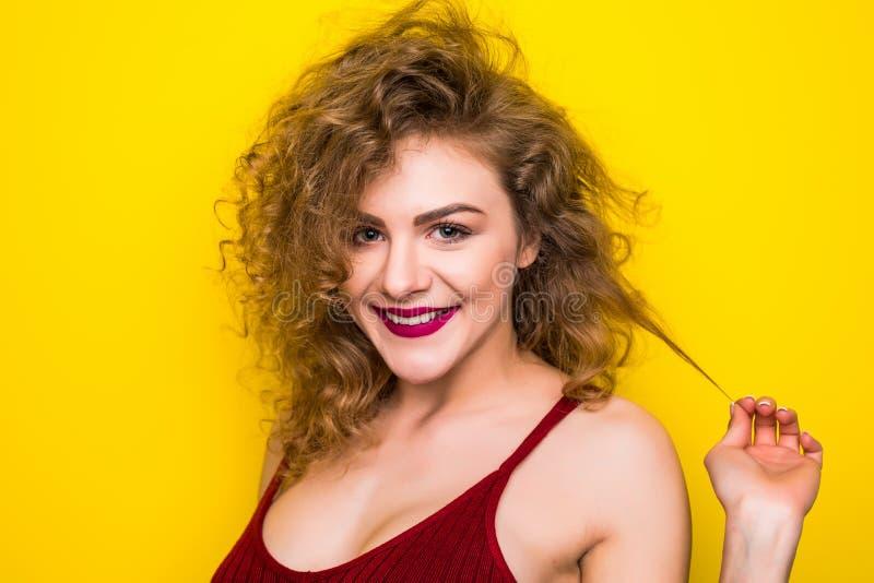 Jeune femme bouclée de beauté posant sur le fond jaune avec le geste différent photos stock