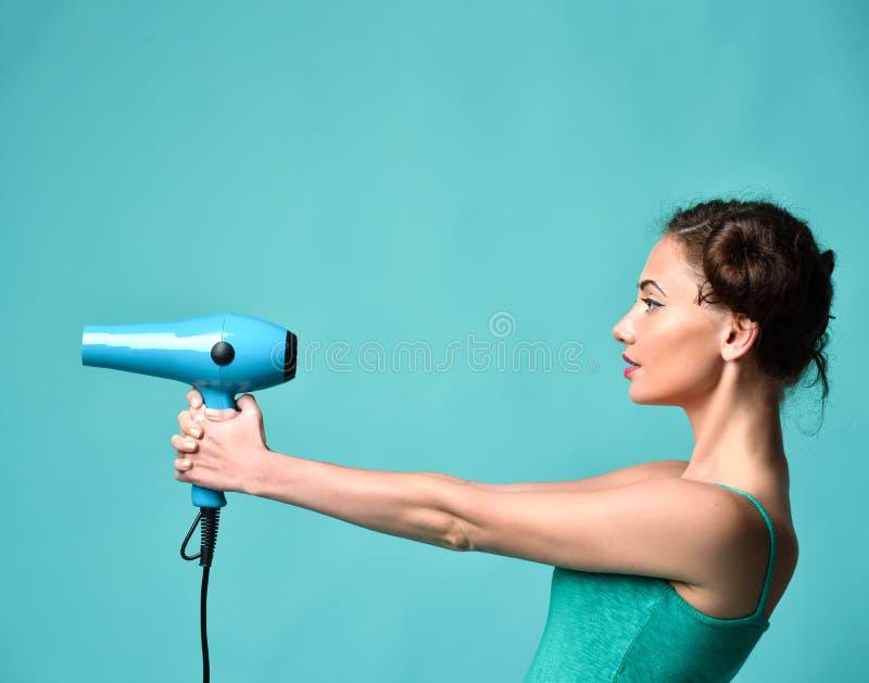 Jeune femme bouclée heureuse de brune avec le sèche-cheveux sur le fond de menthe de bleu photo libre de droits