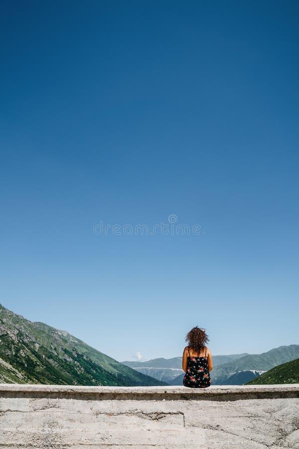 Jeune femme bouclée reposant et regardant la vue image stock