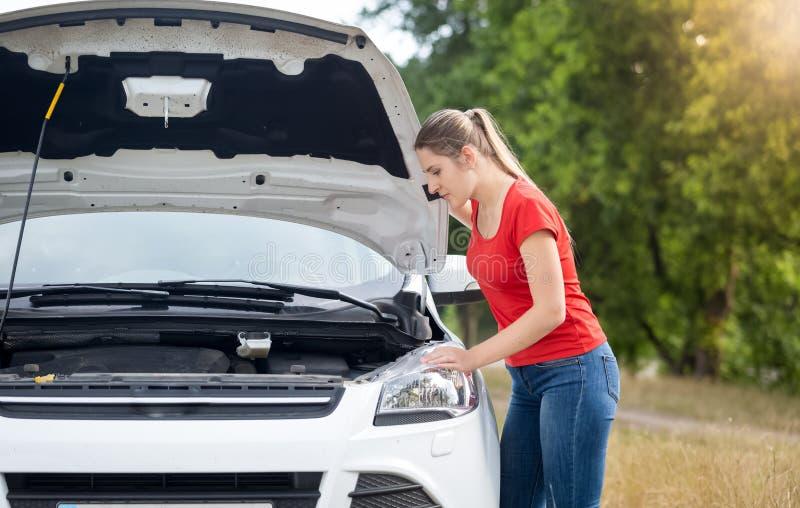 Jeune femme bouleversée regardant sur le moteur surchauffé de sa voiture cassée images stock