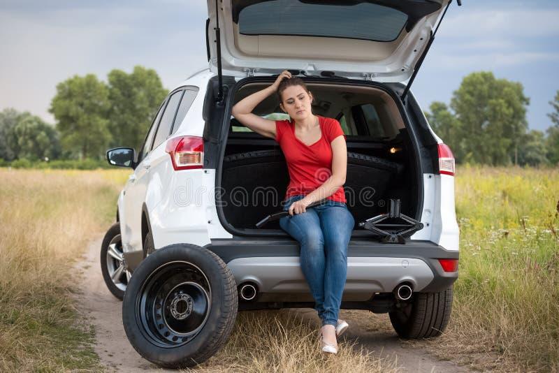 Jeune femme bouleversée s'asseyant dans le tronc de voiture ouvert et l'aide de attente pour changer le pneu crevé images stock