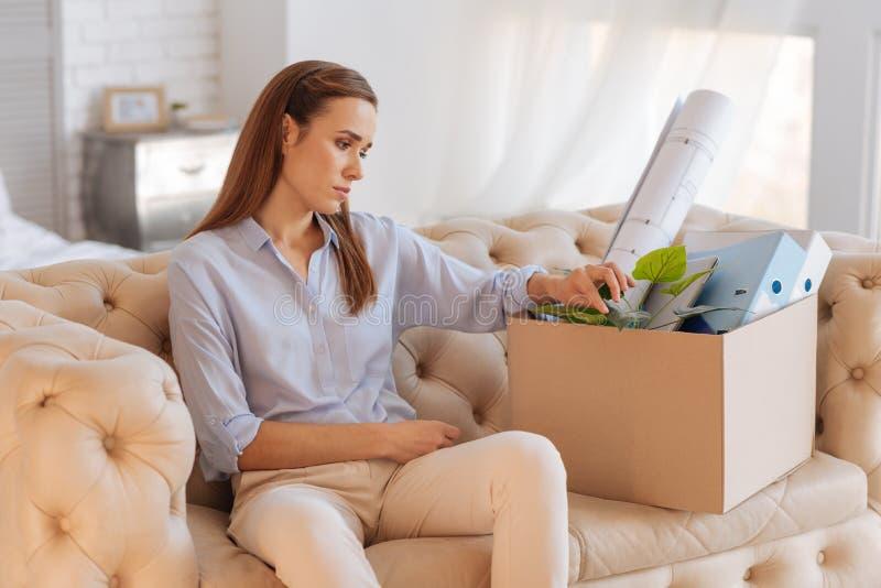 Jeune femme bouleversée s'asseyant pensivement près de la grande boîte images stock