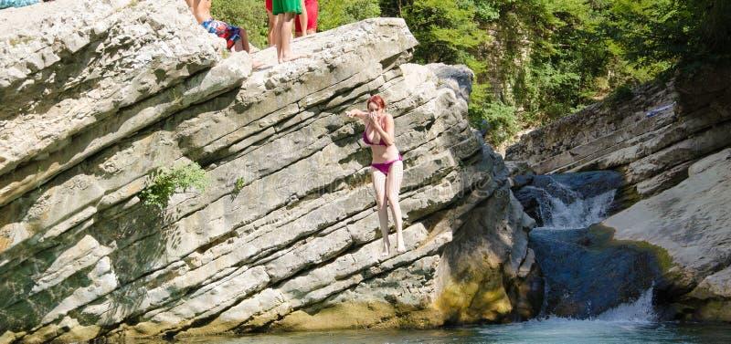 Jeune femme branchant dans l'eau photo stock
