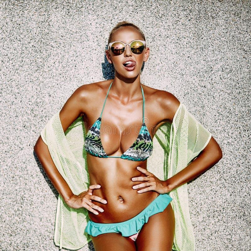 Jeune femme bronzée chaude sexy dans les lunettes de soleil et le maillot de bain montrant t images libres de droits