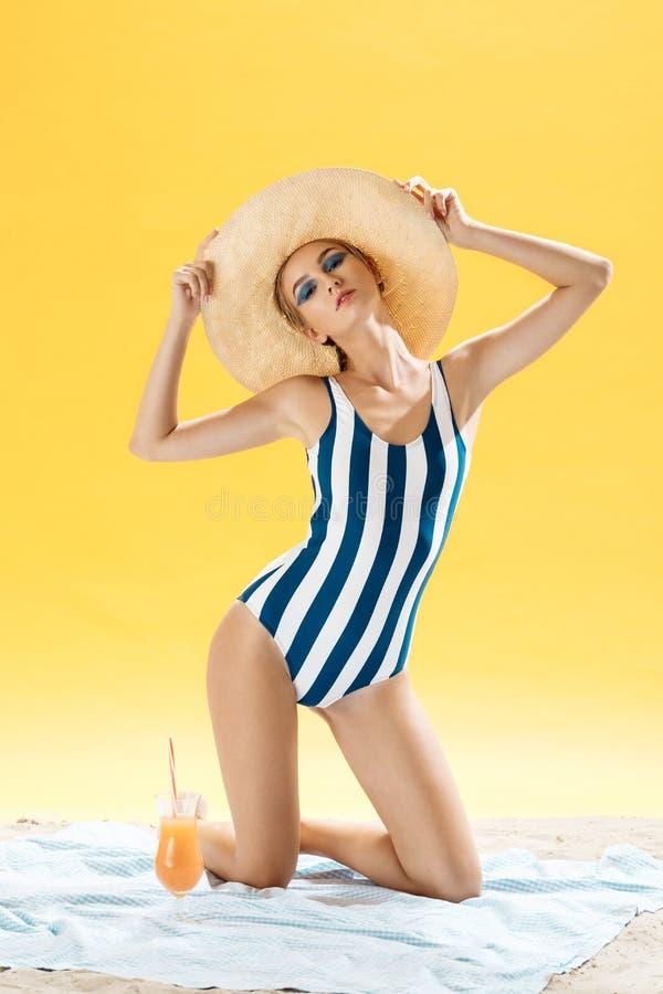 Jeune femme bronzée prenant le bain de soleil malsain un jour d'été sur une plage se cachant du soleil avec le chapeau de paille  image libre de droits