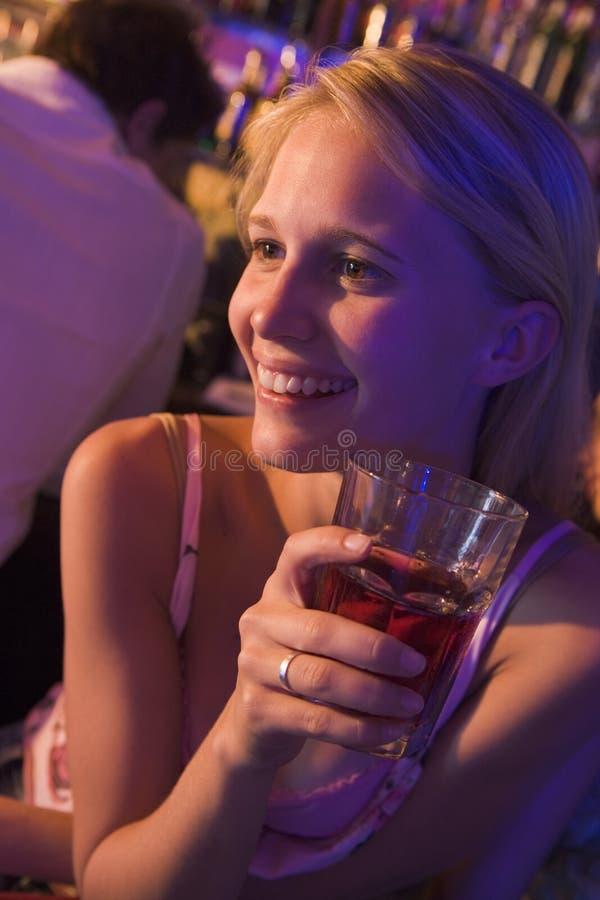 Jeune femme buvant à une boîte de nuit images stock