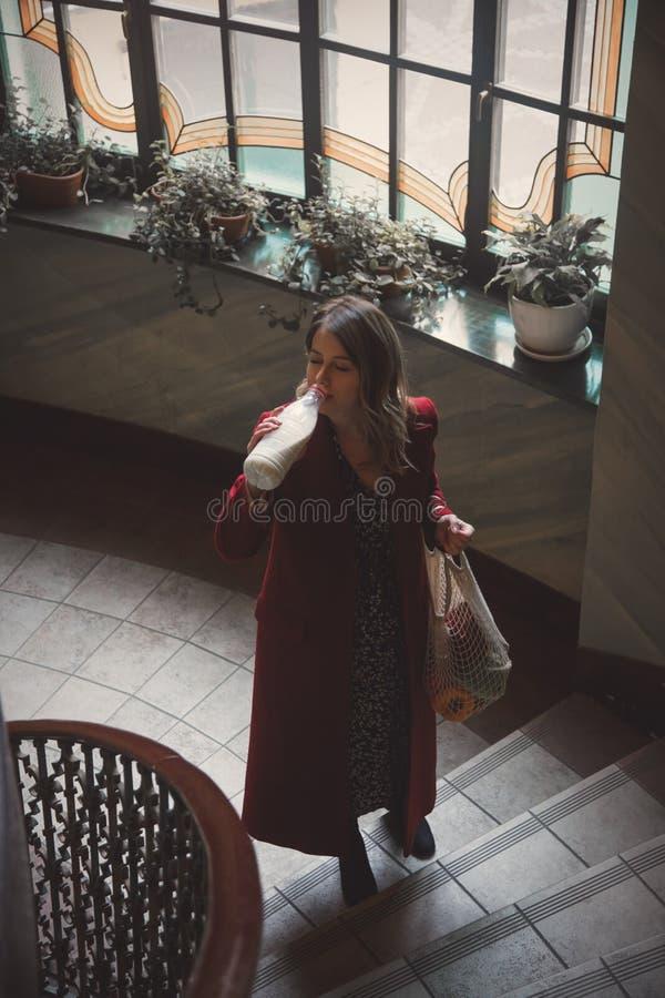 Jeune femme buvant d'un lait et tenant un sac photos stock