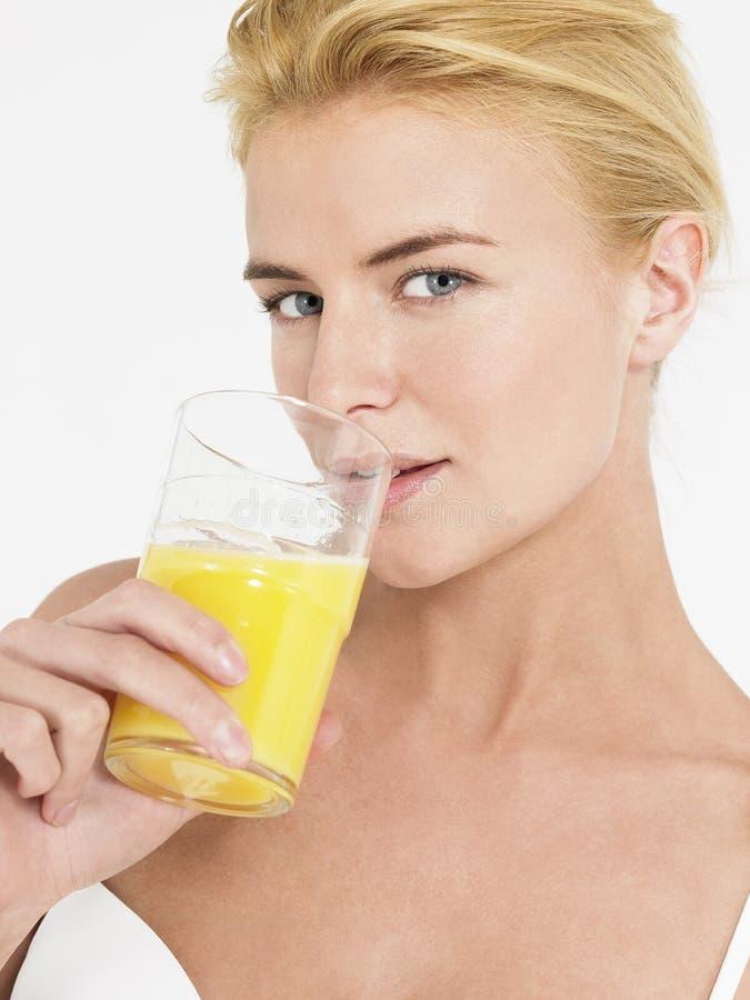 Jeune femme buvant du jus d'orange photographie stock