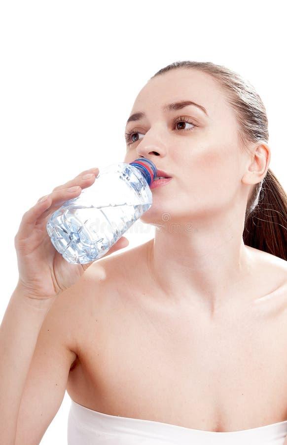 Jeune femme buvant la bouteille d'eau minérale. photos stock