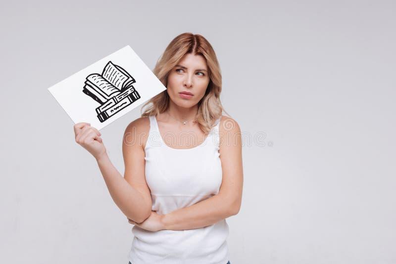 Jeune femme calme fronçant les sourcils tout en se rappelant l'auteur d'un livre intéressant images stock