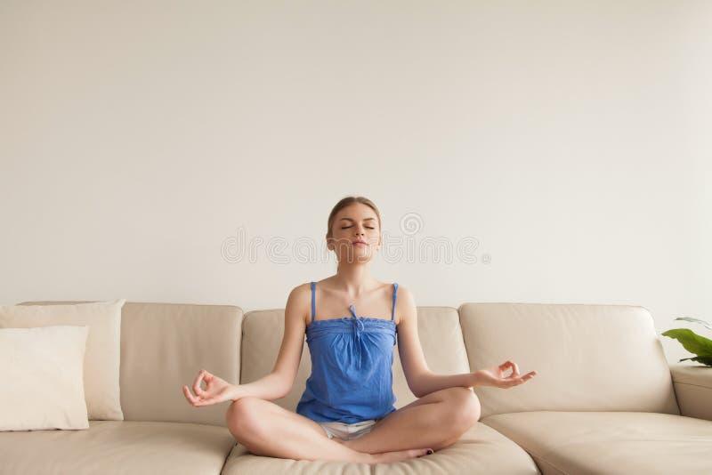 Jeune femme calme méditant à la maison sur le sofa, yoga de pratique images libres de droits