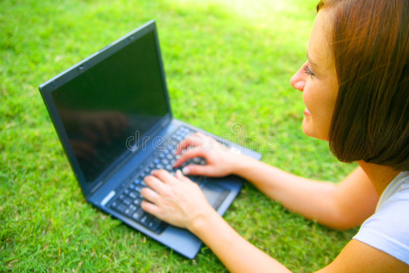 Jeune femme caucasien à l'aide de l'ordinateur portatif extérieur photos stock