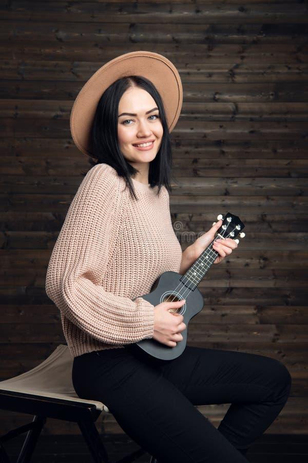 Jeune femme caucasienne émotive attirante dans le chandail et le chapeau de cou de petit pain chantant passionément et jouant l'u photographie stock