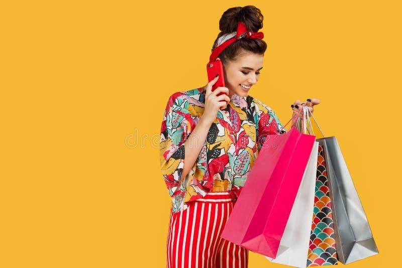 Jeune femme caucasienne attirante dans des v?tements color?s occasionnels tenant des sacs et des achats et entretien sur le smart image libre de droits