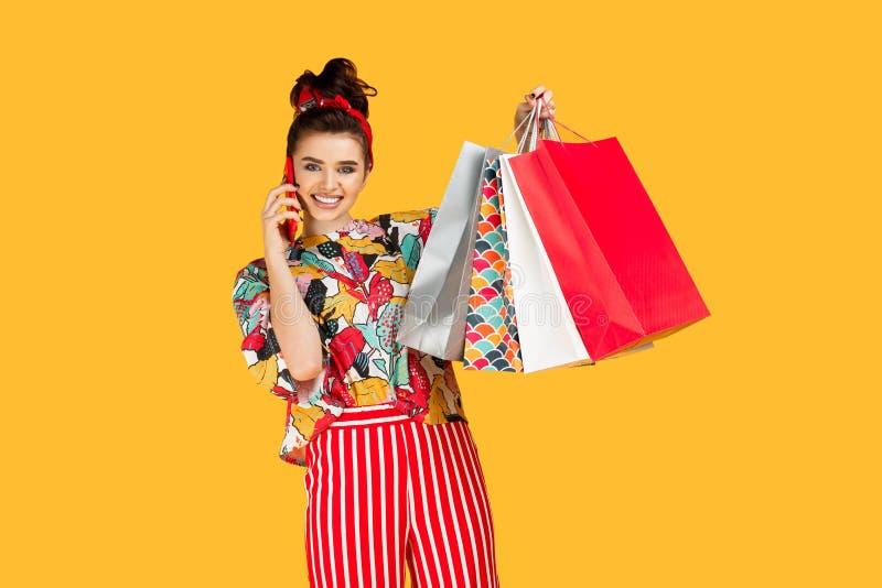 Jeune femme caucasienne attirante dans des v?tements color?s occasionnels tenant des sacs et des achats et entretien sur le smart photographie stock libre de droits