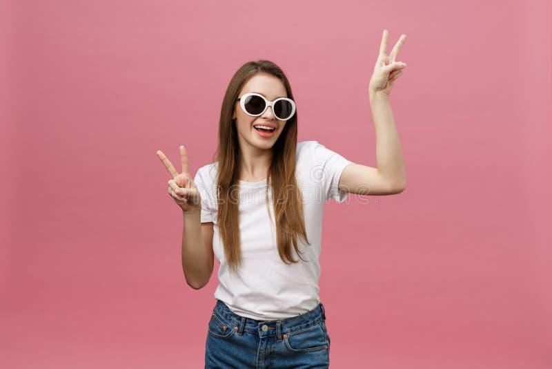 Jeune femme caucasienne au-dessus du regard de sourire d'isolement de fond à la caméra montrant des doigts faisant le signe de vi images libres de droits