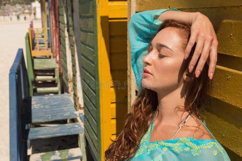 Jeune femme caucasienne avec des yeux se penchant contre la hutte de plage photos stock
