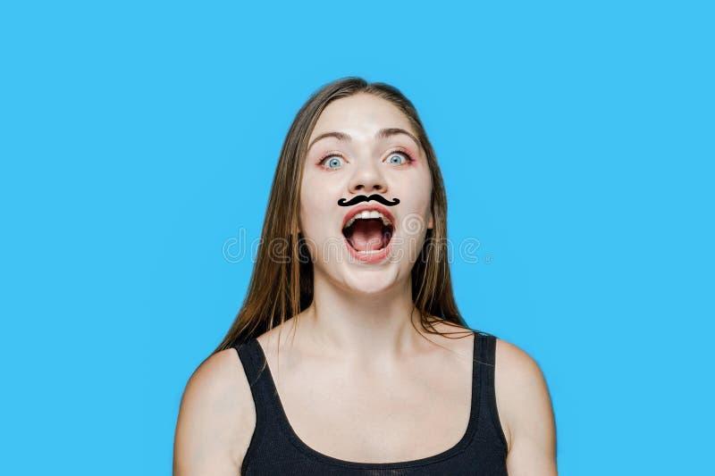 Jeune femme caucasienne avec la moustache tirée sur ses cris perçants de visage, ouvrant la bouche image stock