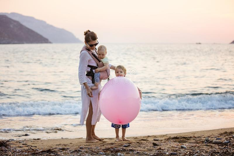 Jeune femme caucasienne avec le fils d'iand de fille de bébé jouant avec le ballon rose énorme sur la plage images libres de droits