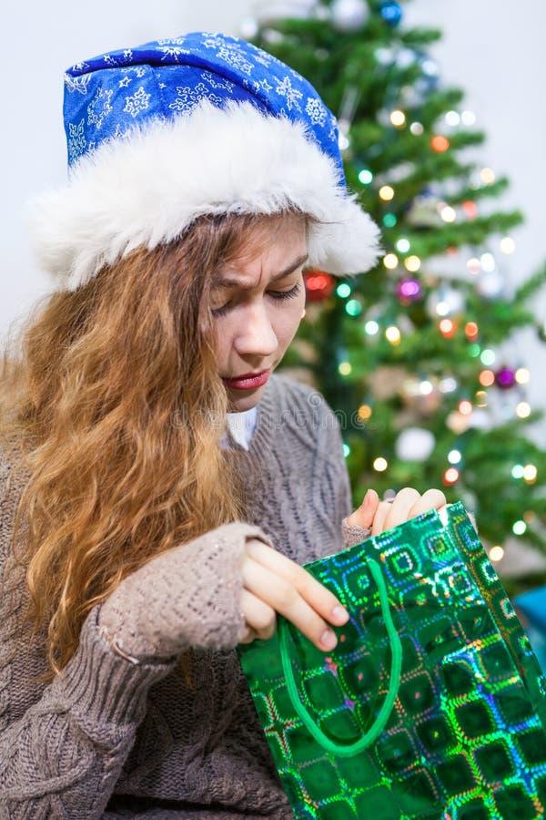 Jeune femme caucasienne déçue regardant dans le sac de cadeau Noël image stock